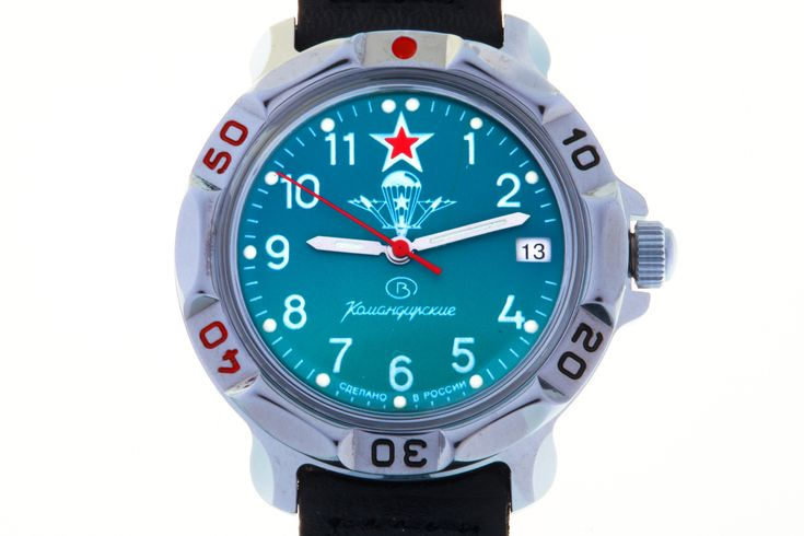 WATCH VOSTOK KOMANDIRSKIE 811307 USSR AIRBORNE TROOPS TINY EMBLEM. At the top of the turquoise face, at the level of twelve-hour point, there is a red five-pointed star with a white border.  In the center, over the hands axis, there is the emblem of the Airborne Forces of the USSR (VDV) – an open parachute with a five-pointed star on the straps and two planers on the sides. #russian #mechanical #military #watches #vostok #komandirskie #gifts #souvenirs #airborne #aircraft #paratrooper