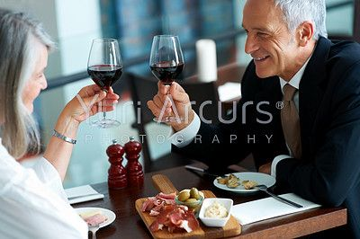 Mature couple enjoying dinner in a restaurant toasting wine glasses - stock photo #54456
