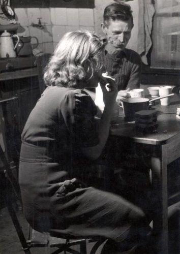Man en meisje eten een boterham aan tafel  in een armoedige keuken. Nijmegen. 15 november 1948. -[Gezinsleven]