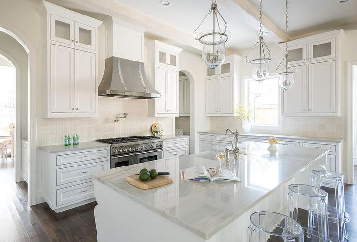 Expansive white kitchen features a row of white cabinets finished with a white quartz countertop fixed beneath a window flanked by white shaker cabinets stacked under glass front display cabinets.