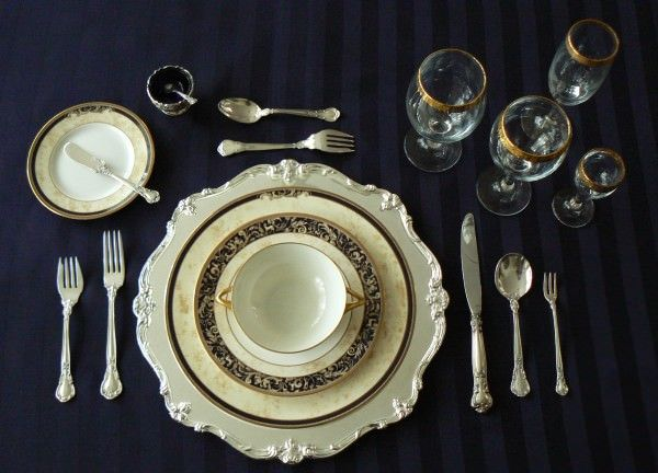 Formal place setting with oyster fork on the right and dessert fork and spoon above the charger