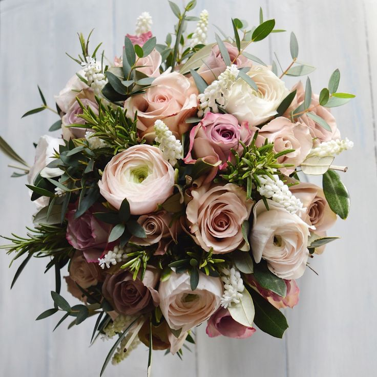 Hand tied Spring Bridal Bouquet of dusky pinks for Farnham Castle Bride created by Eden Blooms Florist.  Made from Hanoi Ranunculus, Rosemary, White Muscari, Memory Lane Rose, Quicksand Rose,nAmnesia Rose, Menthe Rose, Olive, Eucalyptus Parvifolia.  Image by Eden Blooms Florist.