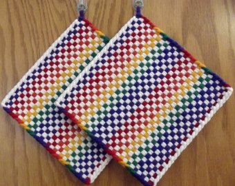 Handmade Retro Style Woven HOT PADS with a Contemporary Look Set of 2  Matching pair of Hot Pads woven in Bright Fiesta Colors of Purple,Red,Orange,Yellow,Green & Blue. Large generous size measuring 8-1/2 x 8-1/2 by 1/4 thick. Both have an aluminum ring in the upper left corner for hanging. Each comes in a sealed sleeve and includes a small 3M Command Hook for easy access.  These are great Hot Pads or Trivets and can be used as a Potholder or just for decoration. *** They c...