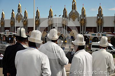Kyrgyz men in their national costumes standing in front of hipodrom, the arena of World Nomad Games