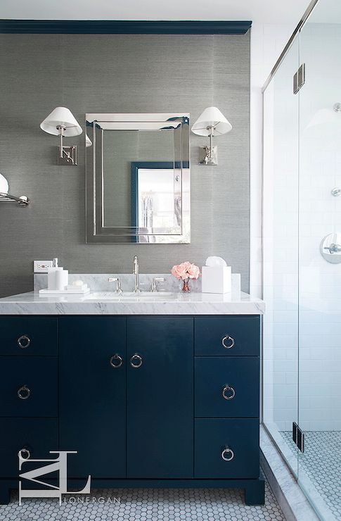 Navy blue and gray bathroom features walls clad in grey grasscloth lined with a polished nickel framed medicine cabinet illuminated by polished nickel sconces accented with white plated shades over a navy washstand with ring pulls topped with white marble alongside a marble hex floor next to a walk-in shower.