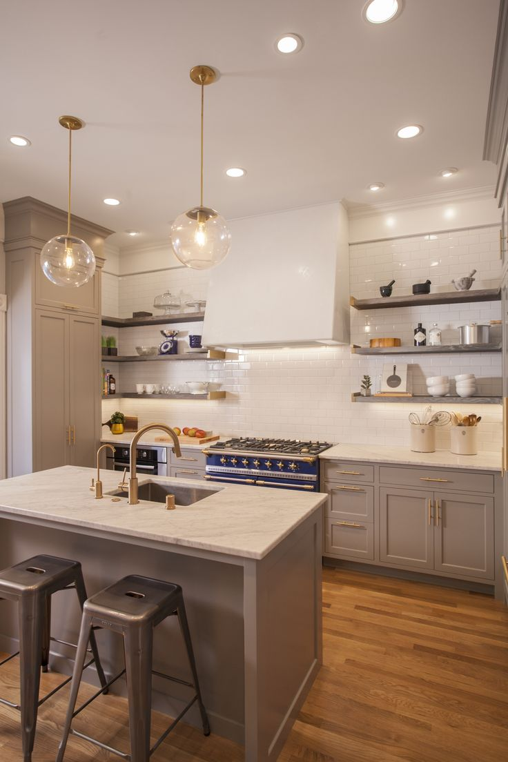 Open shelving with brass ends, clean white tiles and a custom veneer hood gives the kitchen its unique feel.