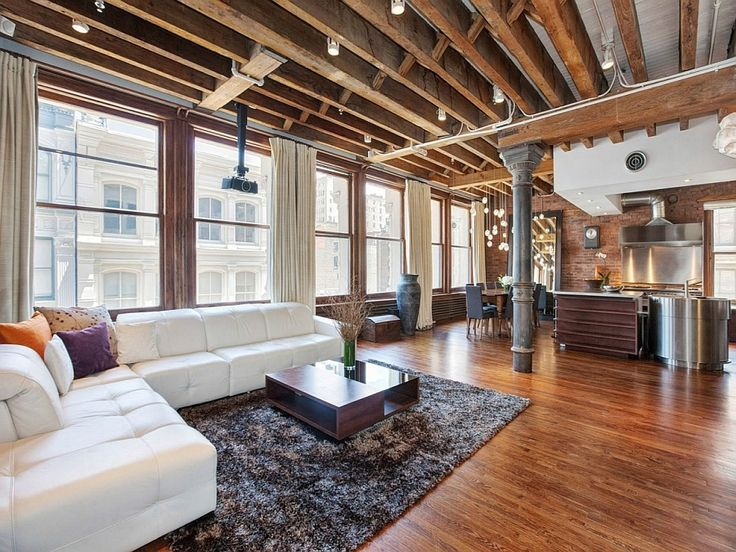 Plush couch in white adds a touch of contemporary class to the room Cozy New York City Loft Enthralls With An Eclectic Interior Wrapped In B...