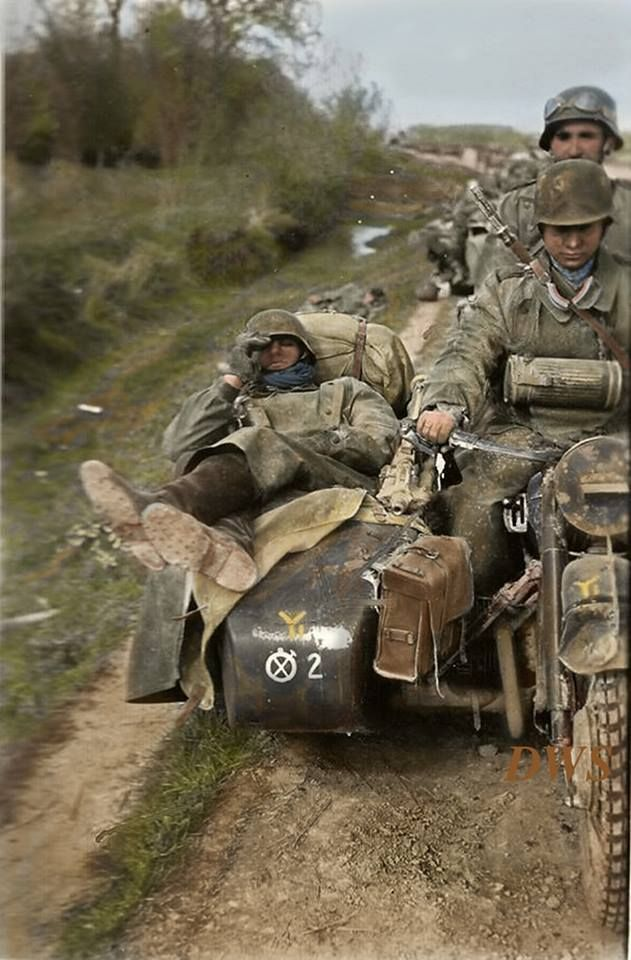 Exhausted Wehrmacht troopers travelling in convoy on a BMW R12 and sidecar of the 2./Motorcycle Infantry Company, 8th Panzer Division, somewhere on the Eastern Front in 1941.