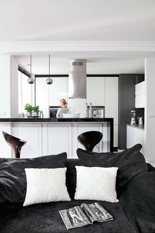 Kuchnia otwarta na salon to wcielenie klasycznej elegancji. I choć lakierowane na wysoki połysk są skrajnie nowoczesne, sztukateryjne wykończenie półwyspu i tapeta na jednej ze ścian dodają jej stylowego posmaku. A duet czerni i bieli aranżacyjnie spina ją z salonem.