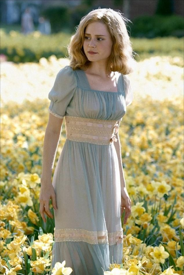 blue and yellow dress, blond hair, brown eyes, in a field of yellow flowers, pensive, concern
