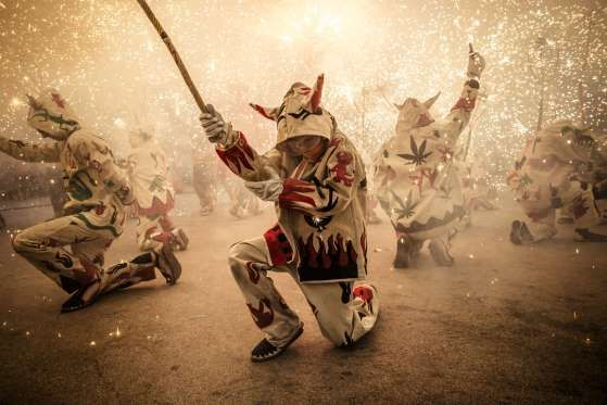 Barcelona, Spain -Children wearing devil costumes dance to traditional drums during the 'correfocs' (fire-runs) at the end of the Festa Major De Gràcia on Aug. 21