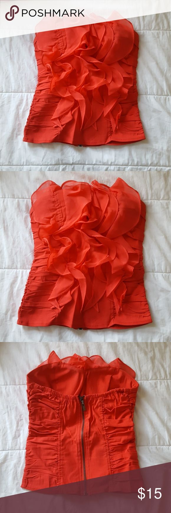 Body Central ruffle tube top Sexy ruffle front tube top from Body Central is labeled orange, but also appears red. Like new and still in packaging, purchased but never worn, so it is in perfect condition. Has a zip back and pad inserts in shelf so it can be worn without a bra. Body Central Tops