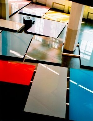 """The artist Adrian Schiess has been exhibiting his trademark """"flat"""" paintings internationally since 1987. These large aluminum panels are rendered in enamel or digital prints covered with lacquer. The paintings are not conventionally hung on the wall. Rather, the artist places the works on the floor or upright against a wall. Their glossy surfaces are intended to reflect the passage of time, light, and people in the environment."""