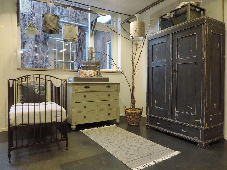Stoere babykamer met donkergrijze kast en lichtgrijze antieke commode, gecombineerd met bronskleurig smeedijzeren ledikant. www.nieuwedromen.nl