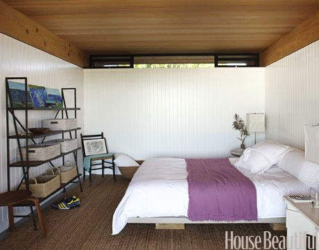 For the guest bedroom of a modernist beach house on Long Island by architect Cary Tamarkin and designer Suzanne Shaker, a simple bed frame was made by stretching painter's linen over a wooden platform.