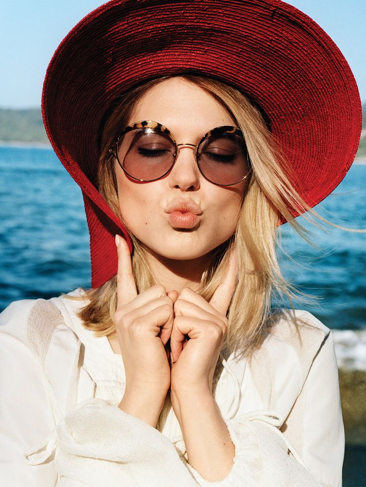 Complement a rosy flush and pink pout with a vibrant red chapeau—the perfect pop of color against floaty summer whites.