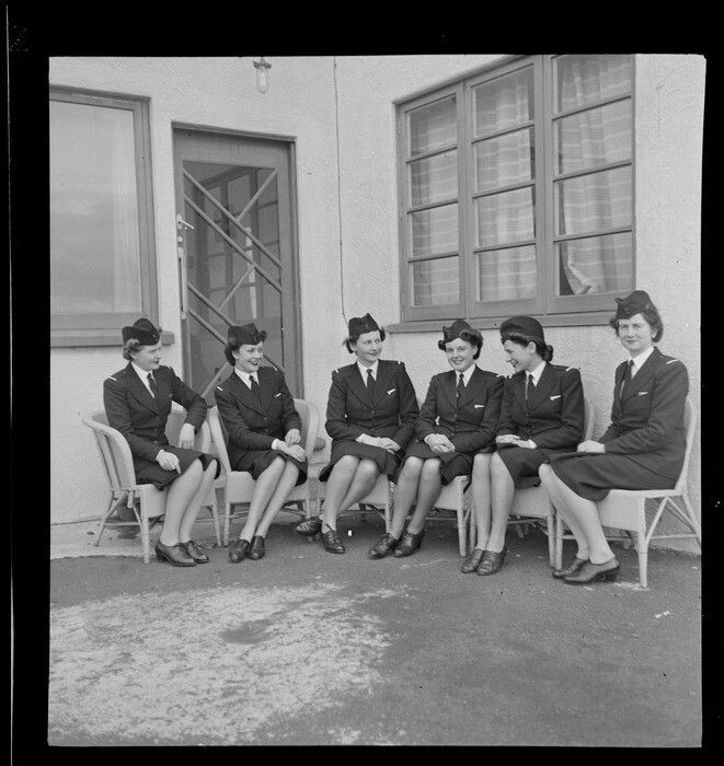 TEAL Tasman Empire Airways Ltd stewardesses, (l to r): Misses [Maynes?], Everand, Beckett, Woolley, Paterson and [Martin?] sitting on cane chairs in front of the door of the TEAL building, Mechanics Bay, Auckland. Date: Aug 1946. Photograph taken by Whites Aviation.