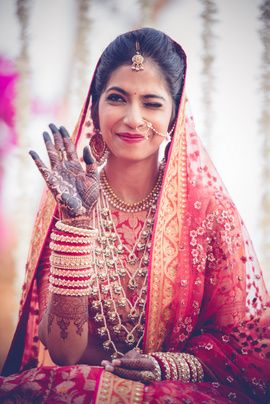 Indian Wedding Jewelry - Candid Shot of the Bride in a Red and Orange Lehenga with Satlada Haar | WedMeGood  #wedmegood #indianbride #indianwedding #bridal #satlada #indianjewelry #jewelry #orange #veil