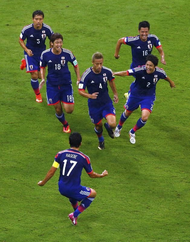 Japan's Keisuke Honda (4) celebrates with teammates after scoring a goal during the 2014 World Cup Group C soccer match between Ivory Coast ...