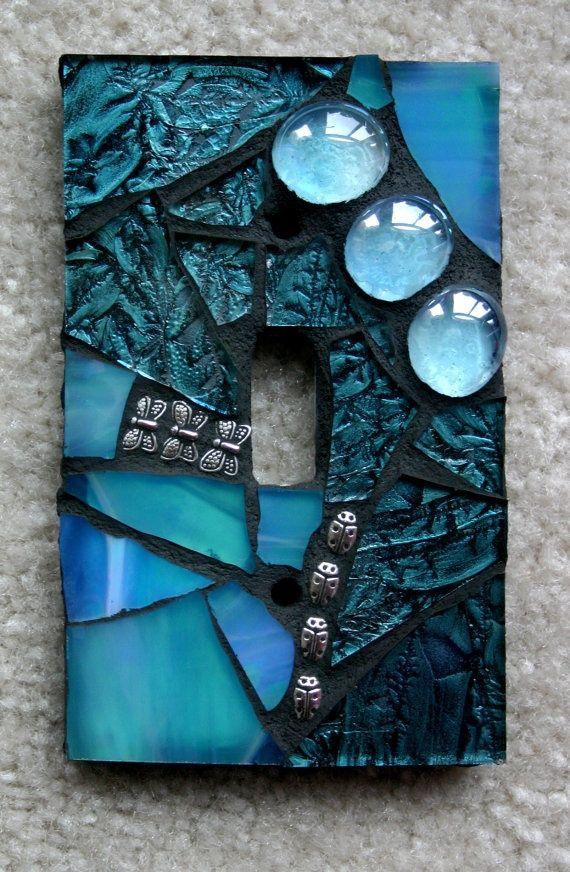 Tapa de luz cubierta con mosaicos, gemas y demás.
