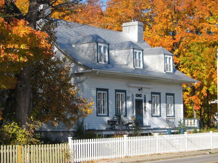 Île d'Orléans, maison québécoise, toit double versant, lucarnes datant de la fin du 18è siècle, symétrie des fenêtres en façade, galerie non couverte.