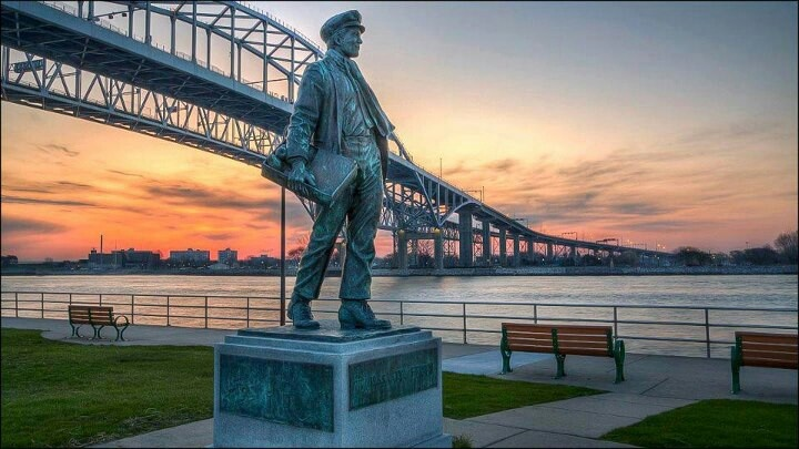 Statue of Thomas Edison as a boy with the Blue Water Bridge in the background in Port Huron, Michigan