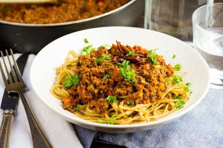 Recept voor klassieke pasta bolognese voor 4 personen. Met zout, olijfolie, peper, ontbijtspek, gehakt, Italiaanse roerbakgroente, gepelde tomaten, zongedroogde tomaten, ui, knoflook en spaghetti (pasta)