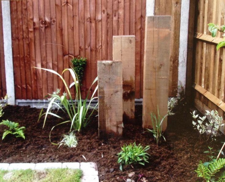 Three upright railway sleepers draw the eye to the corner of the garden