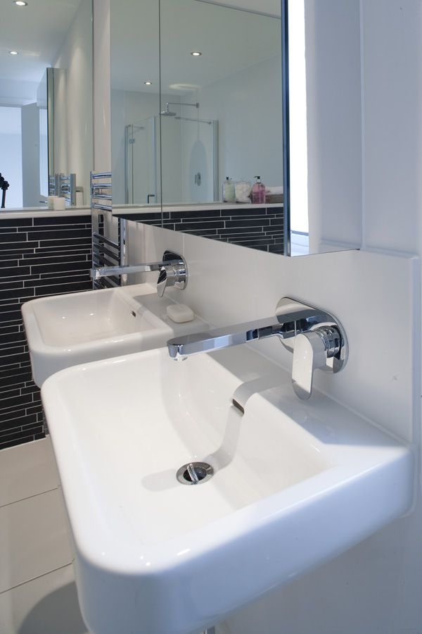 Life wall mounted basin mixers by VADO in a bright and airy black and white bathroom.