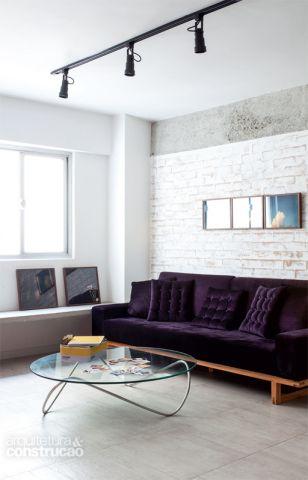 Como a parede original ficava mais recuada, foi substituída por uma nova de tijolos alinhada à viga e finalizada com uma demão de Texturatto Especial (Suvinil) com efeito de concreto. Sob a janela, bancada de concreto chumbada à parede, 50 cm acima do piso, apoia quadros ou serve de banco. Para realçar o clima de estúdio, a arquiteta Mariana Andersen escolheu o trilho com quatro spots de alumínio preto da altena (Yamamura, por r$ 489). Mesinha Futon Company.