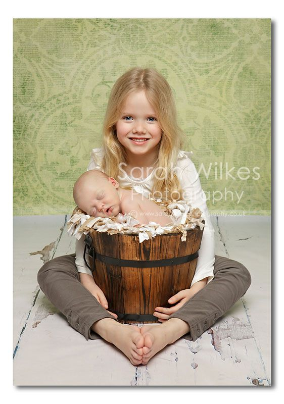 I love the basket idea. Have the siblings surround basket-one shot smiling @ camera, one shot looking at baby