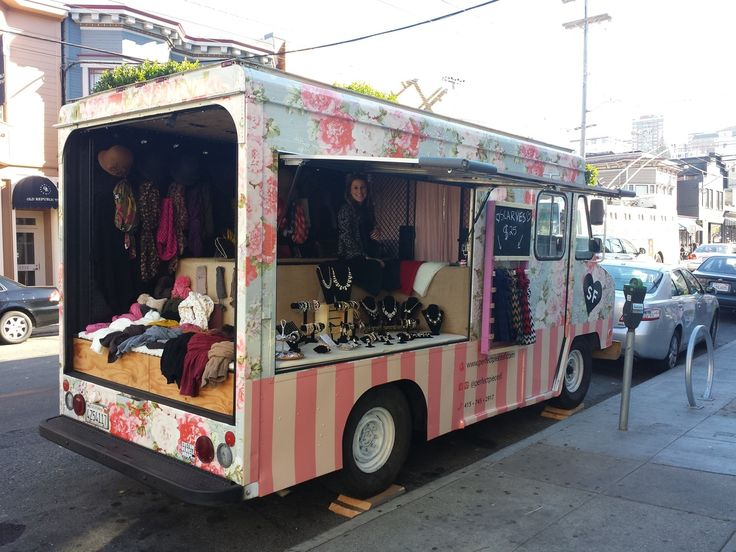 A Mobile boutique with a chic flowery exterior. Complete from outfits to accessories!