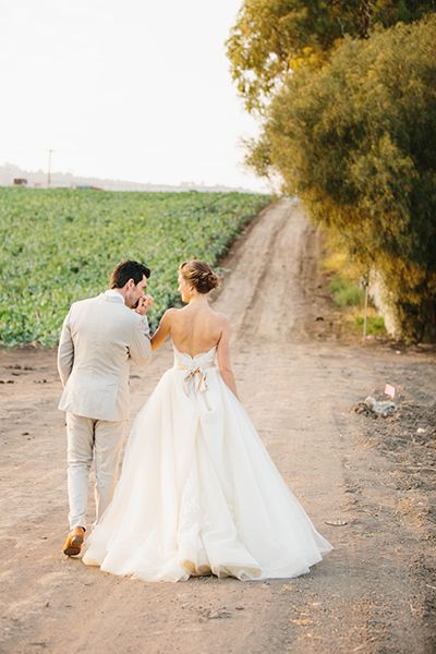 Love this romantic wedding photo of the bride and groom walking down a path together
