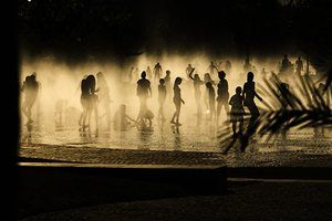 People cool down in a fountain beside the Manzanares river in Madrid, Spain. Weather stations are warning people to take extra precautions as a heatwave engulfs much of the country