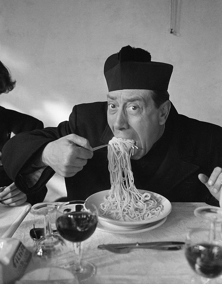 """1952. Pause déjeuner sur le tournage du deuxième film de la série des Don Camillo """"Le retour de Don Camillo"""". L'acteur Fernandel se régale en mangeant des spaghettis accompagnés d'un verre de chianti. Fernandel tournera six Don Camillo mais ne pourra pas terminer le dernier en raison d'un cancer qui va l'emporter l'année suivante . Le 18 janvier 1953 alors qu'il était à Rome avec sa fille Jeanine le pape Pie XII le pria de venir au Vatican afin de faire la connaissance du plus connu des…"""