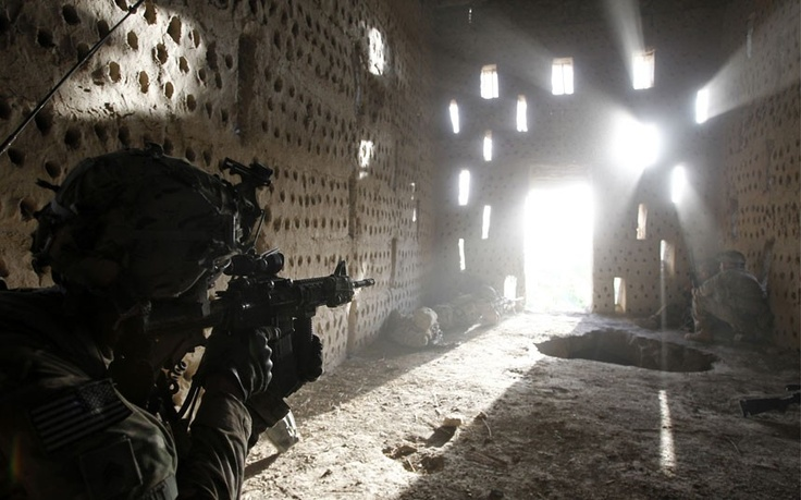 U.S. soldier Nicholas Dickhut from 5-20 infantry Regiment points his rifle at a doorway after coming under fire by the Taliban while on patrol in Zharay district in Kandahar province, southern Afghanistan