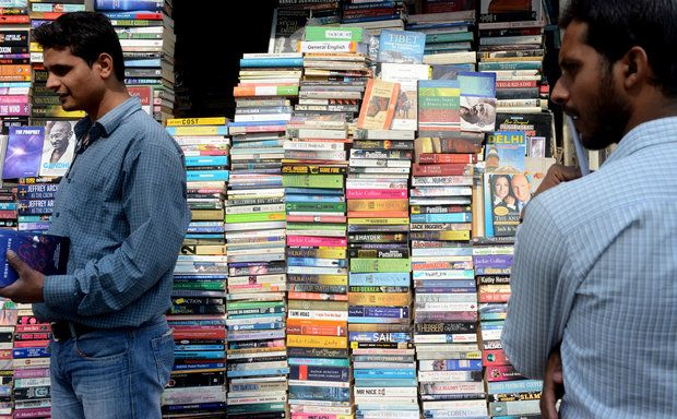 Shoppers browse books in multiple languages at an outdoor stall in New Delhi.