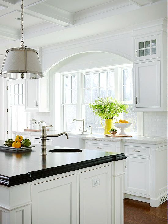 Island Features A large island is the focal point of this kitchen. Wide pilasters at each corner of the island and a dark mahogany countertop give the island an old kitchen table look. Space for working in the kitchen is complete with a built-in sink only steps away from the kitchen's main sink and other appliances. The arched detail above the main apron-front sink balances the square, rigid lines of the coffered ceiling.