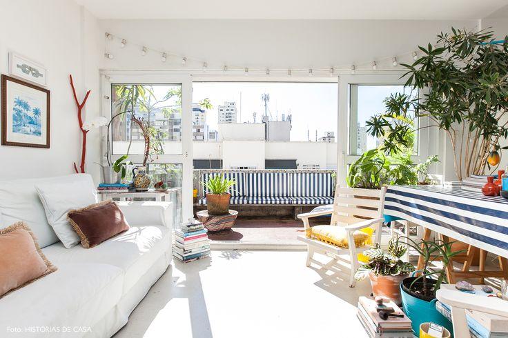 Apê com clima praiano tem varanda com plantas e sofá e poltronas brancas.