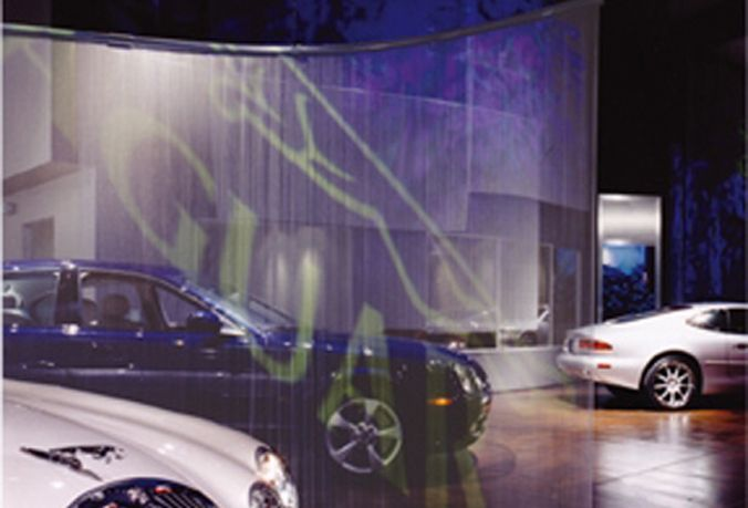Woven wire meshing by Cascade Coil providing the perfect backdrop for the Aston Martin Jaguar of Tampa video projection display.