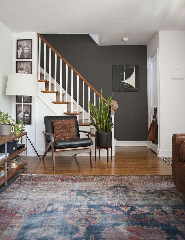 A Modernized Charmer For Creatives in Pennsylvania | Design*Sponge | eclectic large entry with staircase and black accent wall
