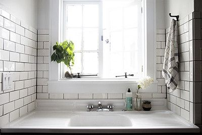 Contemporary Rustic Scandinavian Kitchen: A wide basin farm-style sink underneath a recessed window..