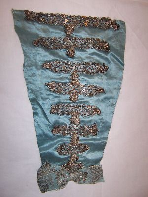 Stomacher : Blue satin over white linen. Triangular piece, trimmed with silver braid with spangles, in horizontal lines. Blue and silver ribbon bow at base. 1760-1770