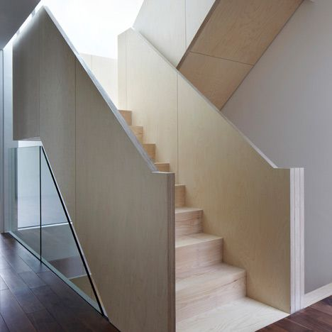 These London townhouses by architects Piercy & Company have chunky banisters formed from thickly layered birch plywood. The stairs zigzag up from the basement floor to the second floor roof terraces of each of the three residences, which are located behind a listed wall within the conservation area of Bloomsbury. The two-storey-high facades of each house are constructed from a