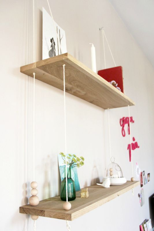 27 innovative ways to decorate your home with books, including this minimal but beautiful rope and wood bookshelf.