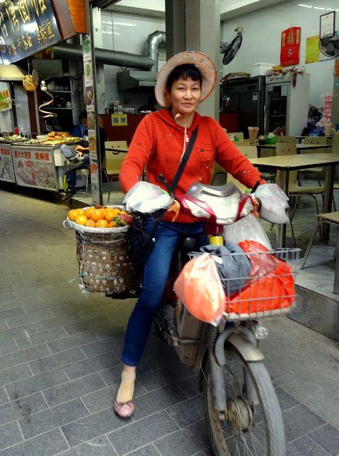 Lady fruit vendor in bike in Zeng Cuo An village.