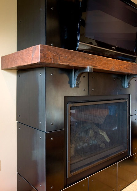 "Designed by MacPherson Construction & Design, the fireplace surround is 3/16"" steel plate panels fastened with rivets. The corbels are hand-forged from 2"" solid steel square bar and the mantel is a reclaimed wood beam. The overall fireplace dimensions are 100"" high by 62"" wide by 20"" deep."