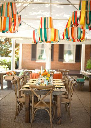 A collection of DIY colorful silk ribbon chandeliers hanging at a Southwestern wedding reception.
