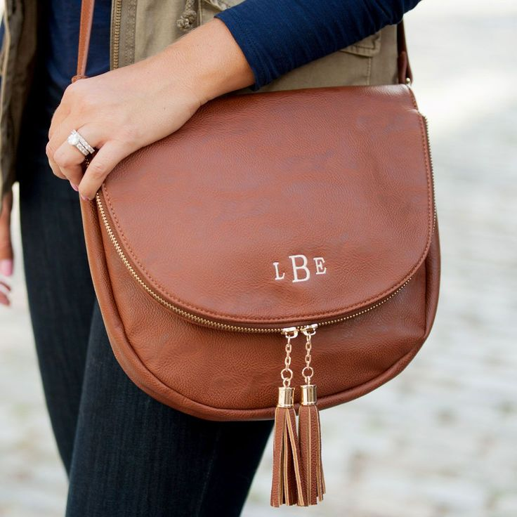 """The most perfect saddle bag for Fall & Winter! Available in black or camel and finished with a classic embroidered monogram. Details 10.5"""" L x 2.5"""" W x 9.5"""""""