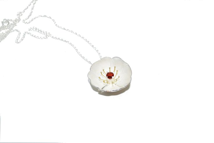 This sterling silver pendant features gold filament that engulfs a striking faceted garnet in the center.#silver #contemporary #unique #London  #designer #jewellery  #NudeJewellery